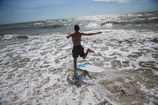 A teenage boy runs into the ocean to catch a wave at the Naples Beach on Sept. 3, 2019. Locals and tourists continue visiting scenic spots in Naples, taking advantage of heavy winds and waves bought on by Hurricane Dorian.