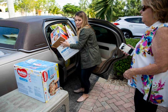 Venue Naples Co-Owner Nicole Roland, left, helps unload over 2,200 diapers from Peggy Moberg's car at Venue Naples on Tuesday, September 3, 2019. Moberg is the president of Naples Wings of Hope, a Collier County charity that was created after Hurricane Irma that focuses on providing basic essentials to those in need.