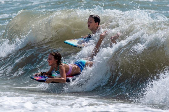 Two teenagers catch a wave near the Naples Beach on Tuesday, September 3, 2019. Locals and tourists continue visiting scenic spots in Naples, taking advantage of heavy winds and waves bought on by Hurricane Dorian.