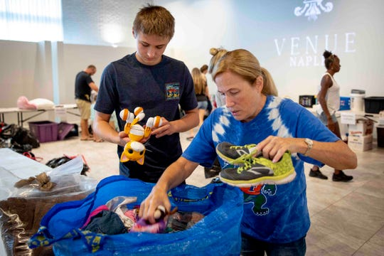 Christopher Fernstrom, 14, left, and Lisa Roland, right, sort through donations that will be taken to the Bahamas in the wake of Hurricane Dorian at Venue Naples on Tuesday, September 3, 2019.