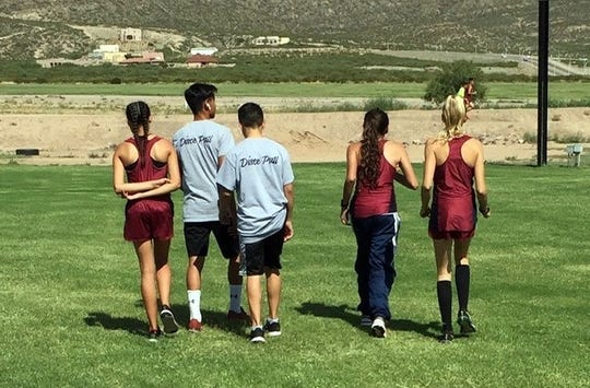 The Deming High cross country runners prepare to warm-up prior to Thursday's races in Alamogordo, NM.