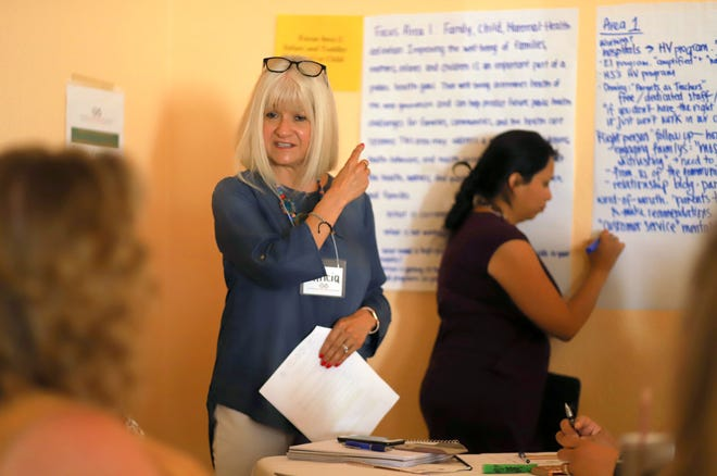 Patricia Latham, director for Center for the Education and Study of Diverse Populations, points to wall charts during Thursday's Early Childhood Development Partnership meeting at the La Fonda Restaurant in Deming.