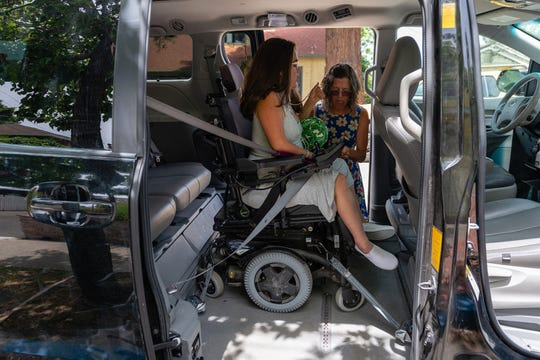 Sylvia Colt-Lacayo's mother, Amy Colt, secures Sylvia's wheelchair inside their van for a day trip to Stanford University. (Heidi de Marco/KHN)