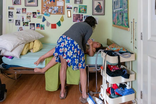 Amy Colt helps daughter Sylvia Colt-Lacayo out of bed on June 24, 2019. Sylvia has a neuromuscular disease similar to muscular dystrophy, leaving her muscles underdeveloped and her legs unable to support any weight. (Heidi de Marco/KHN)