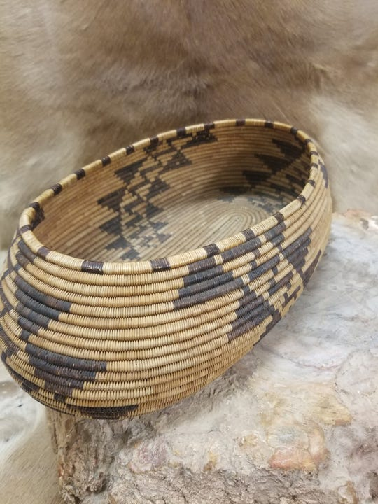 A traditional native American basket with geometric earthtone pattern.