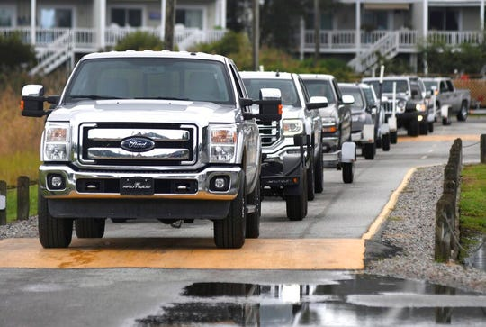Trucks line up at the N.C. Resources Commission boat ramp in Wrightsville Beach, N.C., Monday, Sept. 2, 2019. Residents were watching Hurricane Dorian as it slowly approaches the Southeastern U.S. (Matt Born/The Star-News via AP)