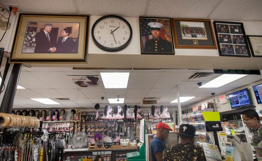 "Daewoo Lee, right, waits on customers in the McClay Street Market in Harrisburg, which he owns with his wife, Aeri. A picture of their son, a Marine serving in the Naval Criminal Investigative Service, hangs near the front door. In one of the photos, the Marine is shaking hands with former President Bill Clinton. They have met Gov. Tom Wolf and like him very much, and Aeri goes on to say, ""Trump has done a lot of good things...he should think before he speaks. But we all make mistakes..."""