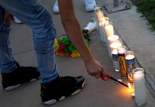 A person attending a vigil for Leilah Hernandez, one of the victims of the Texas shootings in Odessa and Midland, lights a candle Monday, September 2, 2019. Photo by Colin Murphey for USA TODAY