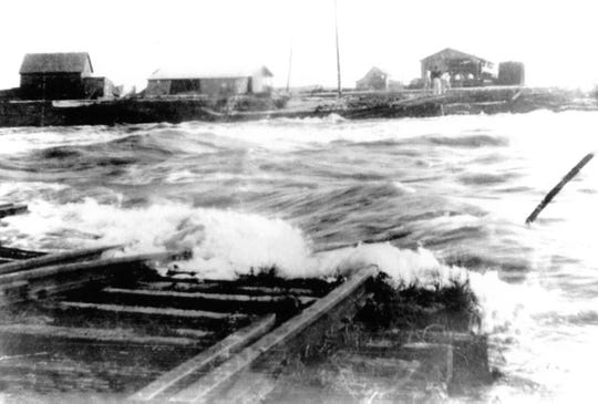 Water rushes by the fishing camps and train tracks in downtown Ocean City after The Storm of 1933 created the inlet connecting the Sinepuxent Bay to the Atlantic Ocean.