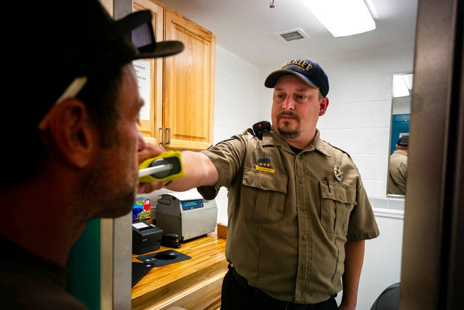 Sgt. Dustin Anthon administers breath tests as part of Weber County's 24/7 Sobriety Program in Ogden, Utah on Thursday Aug. 22, 2019. (Trent Nelson/The Salt Lake Tribune via AP)