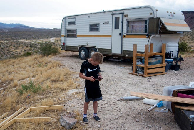 In this Aug. 7, 2019, photo, provided by KUER-FM, Seren Stahr is photographed in front of his family's camp trailer, near St George, Utah. The Stahrs have struggled to find and keep long-term housing in Washington County. They've been living in their camper on public lands for several months. As the new school year begins, Washington County is struggling to support its growing population of homeless students, KUER reports. (David Fuchs/Courtesy of KUER via AP)