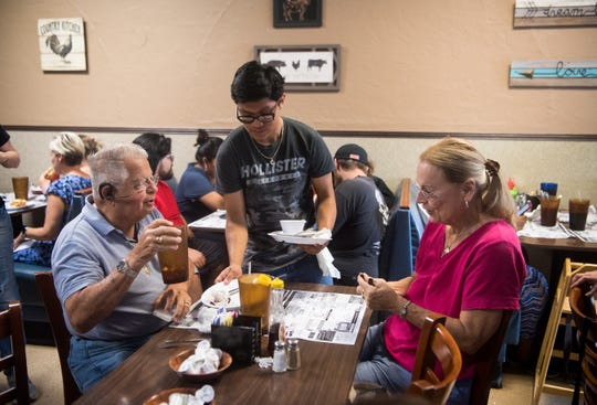 Terry Hurtt (left) and wife Joanne Hurtt, of Stuart, get served breakfast by Roberto Ramirez, 17, of Stuart, at Morning Glory Cafe in Stuart on Tuesday, Sept. 3, 2019, as area residents track Hurricane Dorian.
