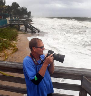 Jack Poling, of Vero Beach, takes photos of the waves and high surf from the deck of Ocean Grill in Sexton Plaza on Tuesday, Sept. 3, 2019, as the outer bands of Hurricane Dorian make their way to the Treasure Coast.