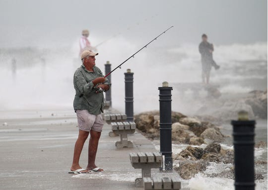 """Doug Jenkins, of Fort Pierce tries his luck fishing off the south jetty as Hurricane Dorian lingers offshore Tuesday, Sept. 3, 2019, in Fort Pierce. """"It's still fishable here"""" Jensen said."""