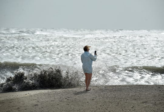 """Robyn Noble, of Fort Pierce records the wave action of the surf on Tuesday, Sept. 3, 2019, as Hurricane Dorian travels slowly off the Treausre Coast. """"I think it's pretty intense and we're waiting for it to move north,"""" Noble said. """"We were here for the last two, this was comparable."""""""