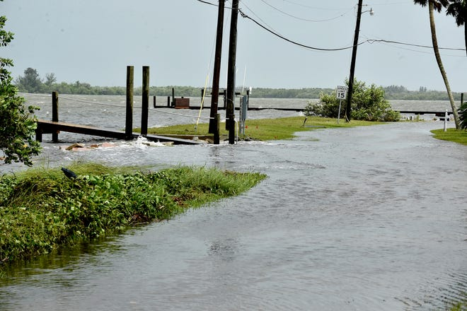 Waves from the Indian River Lagoon cross over into the roadway of North Indian River Drive, a private road in the neighborhood of St. Lucie Village, on Tuesday, September 3, 2019, because of the rain from hurricane Dorian.