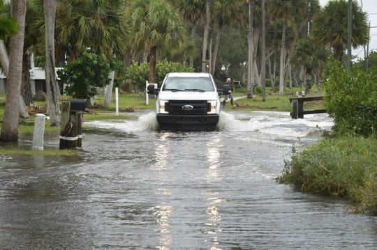 A truck makes its way through the flooded area of North Indian River Drive southbound towards Chamberlain Boulevard, as waves from the Indian River Lagoon contribute to the flooding of the road because of Hurricane Dorian Tuesday, Sept. 3, 2019, in St. Lucie Village north of Fort Pierce.