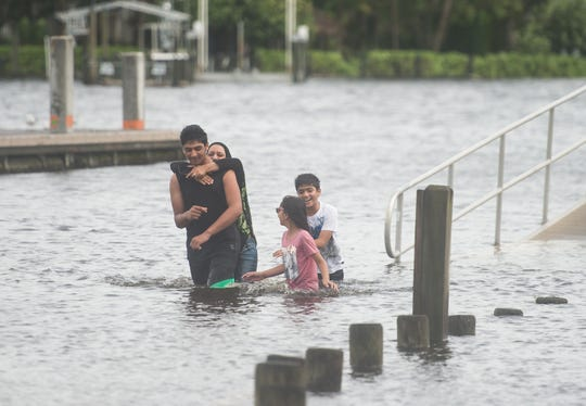 Ayaan Latif, 15, carries his mother, Saima Rashid, through high-level water, while siblings Parisa Latif, 9, and Rayan Latif, 12, follow behind while enjoying time at Sandsprit Park in Martin County on Tuesday, Sept. 3, 2019, while still keeping an eye on Hurricane Dorian's track.