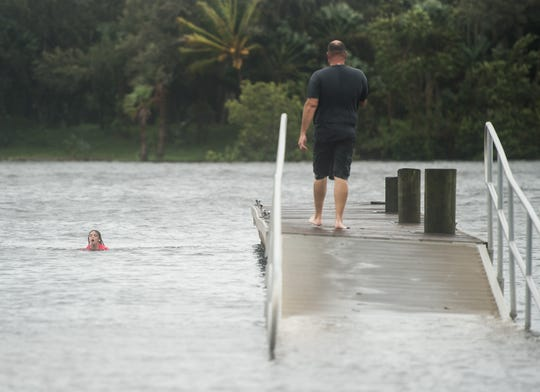 """Kevin Kelley, of Martin County, walks out to watch his daughter, Kaitlyn Kelley, celebrating her seventh birthday, swim in the high level of water at Sandsprit Park in Martin County on Tuesday, Sept. 3, 2019, while area residents keep an eye on Hurricane Dorian's track. """"I did some flipping, and I jumped off the dock from the very end,"""" she said, """"and then we kept jumping, and then our friends were going to come, but then they were scared to jump… it's not scary, it's just deep."""""""