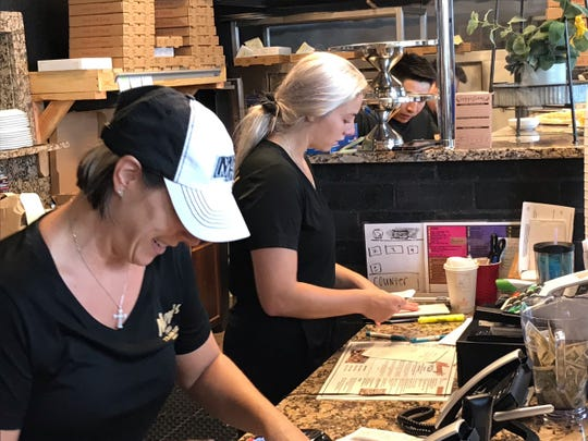 """Michelle Nancy Hanner, owner of Nancy's Pizza at U.S. 1 and Kanner Highway in Stuart, takes customers' orders Tuesday, Sept. 3, 2019, with her daughter, Nancy Michelle Hanner. The elder Hanner said she kept the restaurant open because """"the weather isn't so bad. If it gets bad, we'll close."""" As one of the few restaurants open in Stuart, business has been brisk; the eatery ran out of food Monday, but a supply truck arrived early Tuesday afternoon."""