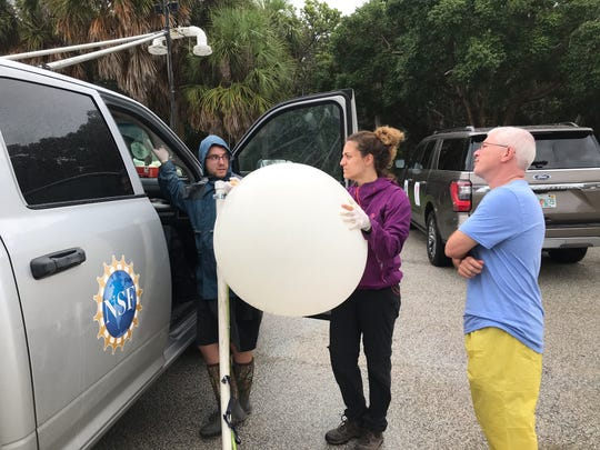 Scientists from the Center for Severe Weather Research in Boulder, Colorado, including Jeffrey Thayer, left, a doctoral student at the University of Illinois; Anna Moral, a doctoral student at the University of Barcelona; and the center's Josh Wurman were at Stuart Beach Tuesday, Sept. 3, 2019, attempting to launch a weather balloon to study the physics of Hurricane Dorian's rain bands.
