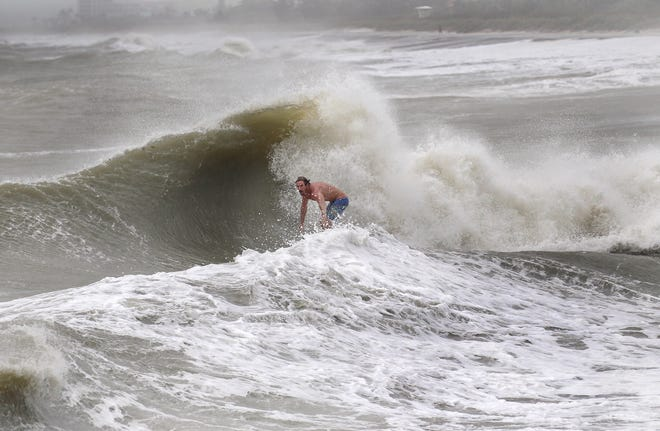 "Surfer Eli Strunk, of Fort Pierce, rides the rough waves of high tide brought on by Hurricane Dorian Tuesday, Sept. 3, 2019, at Fort Pierce Beach. ""It's a little rough, we got a lot of wind and some seas but all things considered, it's kind of fun, not as big as I thought it was going to be,"" Strunk said. ""They only come a few times a year so we try to get them when we can."""