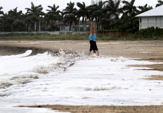 Dan Cooley, of Fort Pierce, does a handstand in the foam of the rough surf crashing over the dune line on Fort Pierce Beach while posing for a friend's picture Tuesday, Sept. 3, 2019, as Hurricane Dorian lurks offshore of the Treasure Coast.