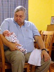Tiffany Ackerman's father holds his youngest grandchild.