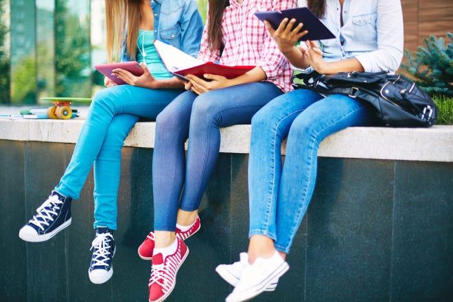 Three girls read outside