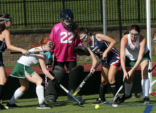 From left, Pleasantville's Ryan Sullivan (12) and Caitlin Rubsamen (24) battle for ball control with Byram Hills' Lizzie Manowitz (15) during field hockey action in Pleasantville's Autism Awareness Tournament at Pleasantville High School Sept. 3, 2019.  Pleasantville won the game 4-0.