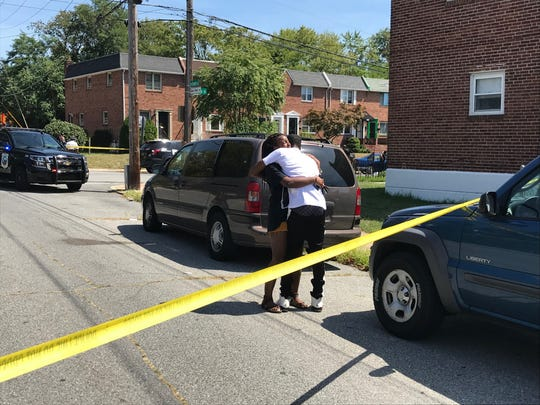 Two people react as Wilmington Police respond to a reported shooting Tuesday afternoon.