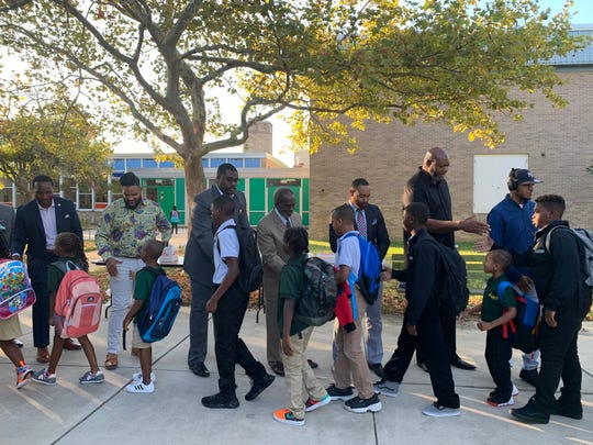"Men in suits greet students at EastSide Charter School, Tuesday as part of a ""Suit Up, Show Up"" program."
