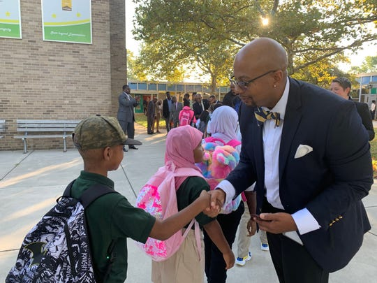EastSide Charter School CEO Aaron Bass greets students as they enter school Tuesday.