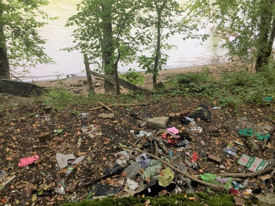 Clothes and trash litter the river bank along Muskingum Avenue, a popular spot where homeless congregate.