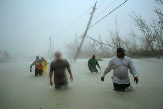 People walk through a flooded road as they try to rescue families near Causarina Bridge in Freeport, Grand Bahama, Bahamas on Sept. 3, 2019.