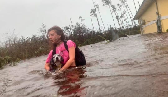 Julia Aylen wades through waist deep water carrying her pet dog as she is rescued from her flooded home during Hurricane Dorian in Freeport, Bahamas on Sept. 3, 2019.