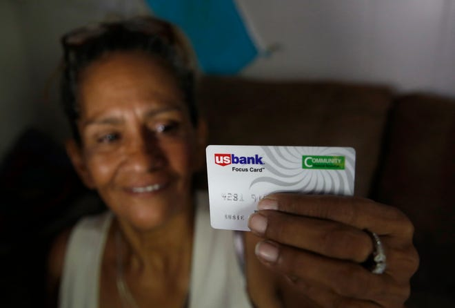 In this photo taken Wednesday, Aug. 14, 2019, Susie Garza displays the city provided debit card she receives monthly through a trial program in Stockton, Calif.