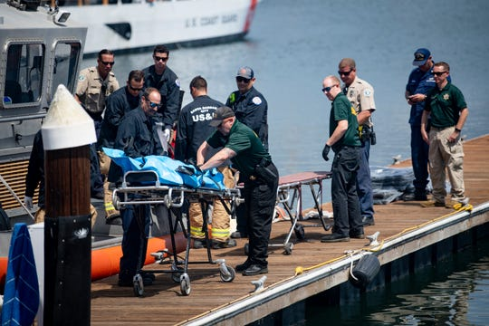 Coast Guard personnel move one of the bodies recovered from the Concecption Monday.