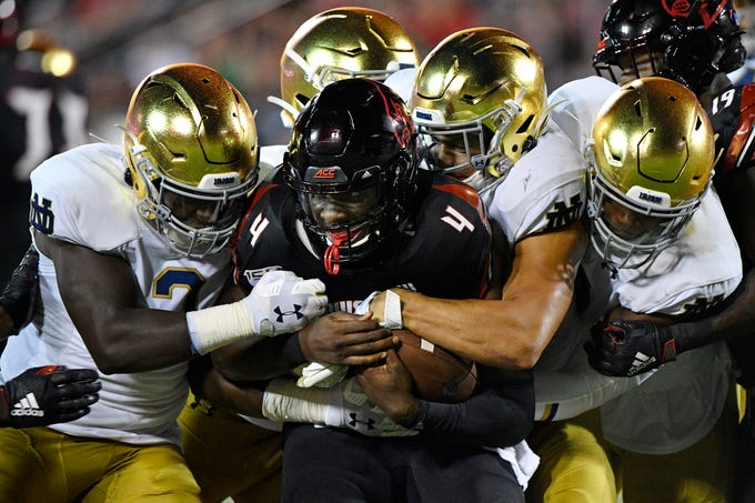 Louisville quarterback Jawon Pass is tackled by a host of Notre Dame defenders during the second quarter at Cardinal Stadium.