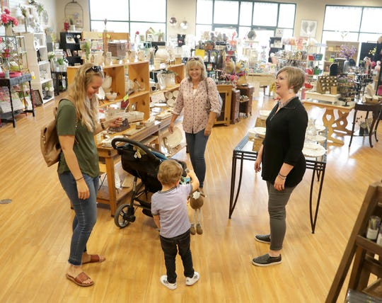 Susan Krahn, owner of Scatter Joy, right, talks with customers in her Grand Chute store.
