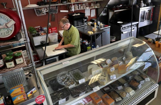 Bob Wall, owner of the Green Gecko in the ground floor of Richmond Terrace, works behind the counter on Wednesday, Sept. 4, 2019, in Appleton, Wis.