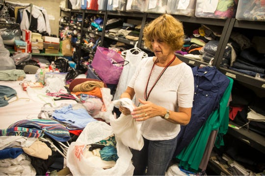 The Gannett Foundation presents a check to Lunch Break, a non-profit food pantry in Red Bank. The pantry provides food and clothing for those in need within our community. Volunteer Sara Langberg sorts through donated clothing.   