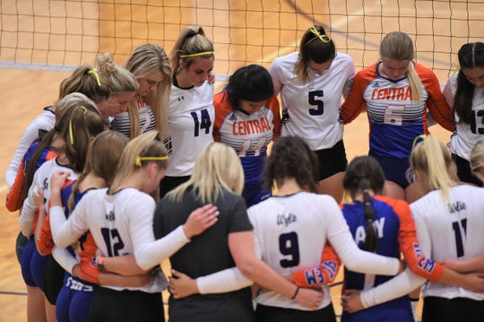 Members of the Wylie and San Angelo Central volleyball teams gather for a moment of silence for the victims of the Odessa shooting before the match at Bulldog Gym on Tuesday. The Lady Bulldogs wore yellow ribbons to honor the Odessa High student who was killed.