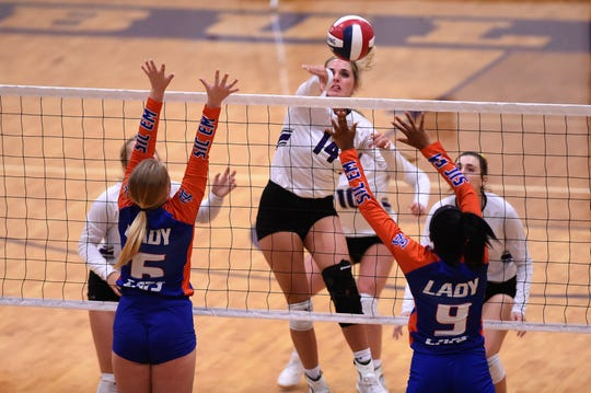 Wylie's Maggie Allen (14) spikes the ball past San Angelo Central's Chelsea Weldon (6) and Kameryn Daniels (9) at Bulldog Gym on Tuesday. The Lady Bulldogs won 25-22, 25-23, 25-17.
