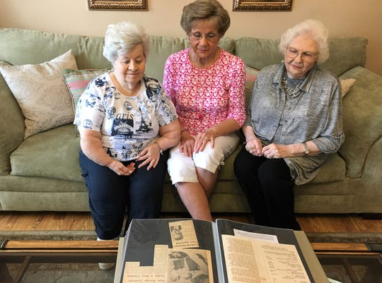 Longtime members of Brook Hollow Christian Church look over a photo album covering 60 years of history. The church will celebrate its 60th anniversary Sunday. From left are Jane Haley Reed, Ann Hawkins and Vi Bearden.