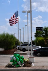 A flag flies at half-staff and a memorial rests in the foreground Wednesday Sept. 4, 2019 at Freedom Buick GMC Truck in Odessa, the site where one of seven people were killed Saturday by a gunman.