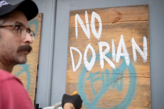 "Brian Di Giorgi paints on the plywood over the windows of his grilled cheese and cocktail bar, Crust, in downtown Wilmington, North Carolina as he prepares for Hurricane Dorian on Sept. 4, 2019. The boards are recycled from Hurricane Florence last year which closed the new business for 22 days. ""As soon as we can be open again, we're gonna be open again,"" he said."