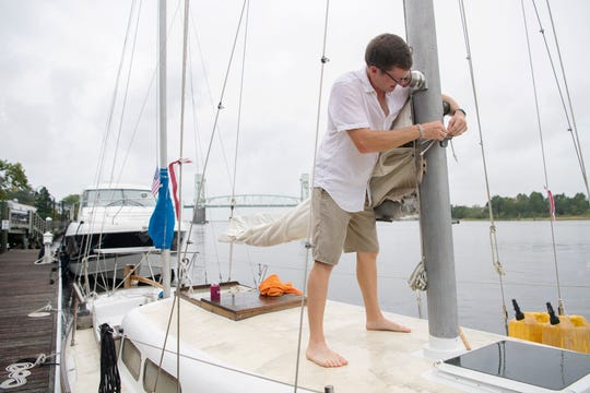 "Captain John Wolfe prepares his sailboat, Maia, for Hurricane Dorian by taking down the sails and moving her further up the Cape Fear River in downtown Wilmington, North Carolina on Sept. 4, 2019. Wolfe bought the boat last year after Hurricane Florence. ""She was one of six boats to survive last year in the marina she was in so she's got good karma,"" he said about Maia."