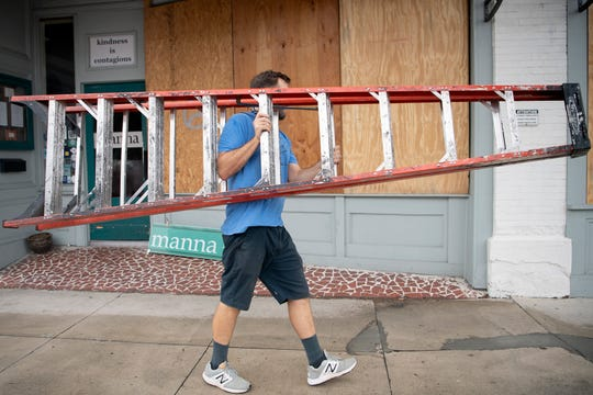 William Mellon, owner of three businesses and a non-profit on Princess Street in downtown Wilmington, North Carolina, moves a ladder as he prepares for Hurricane Dorian to arrive on Sept. 4, 2019.