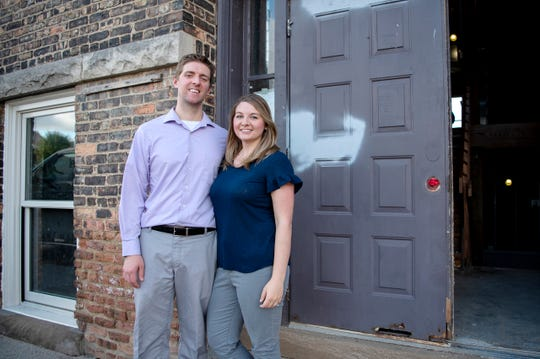 Battle Creek couple Cody and Caitlynn Newman, who created Restore (269), pose for a portrait outside of the now historical landmark The Record Box on Wednesday, Sept. 4, 2019.